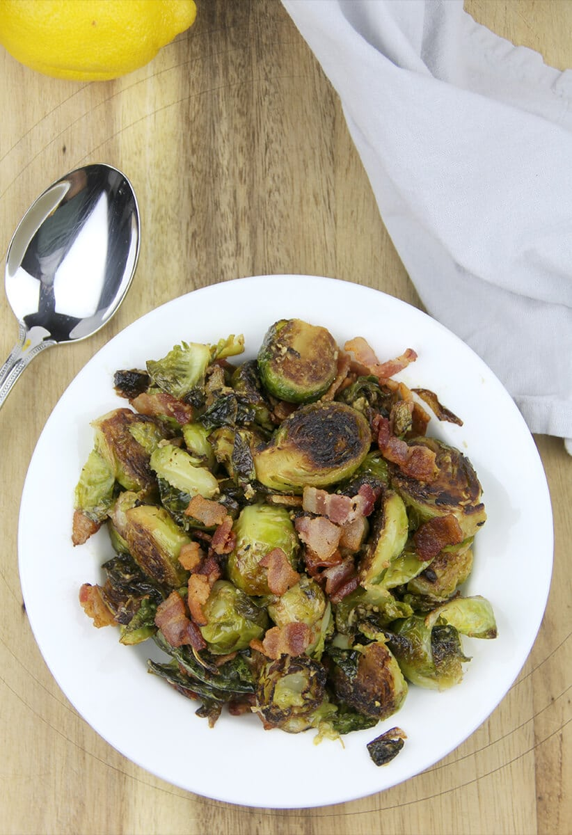 Overhead shot of sauteed brussels sprouts in a dish ready to serve with a spoon resting beside the plate.