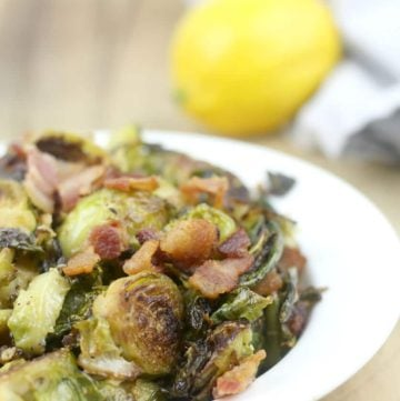 Serving of sauteed brussels sprouts in a white dish with bacon and a lemon.