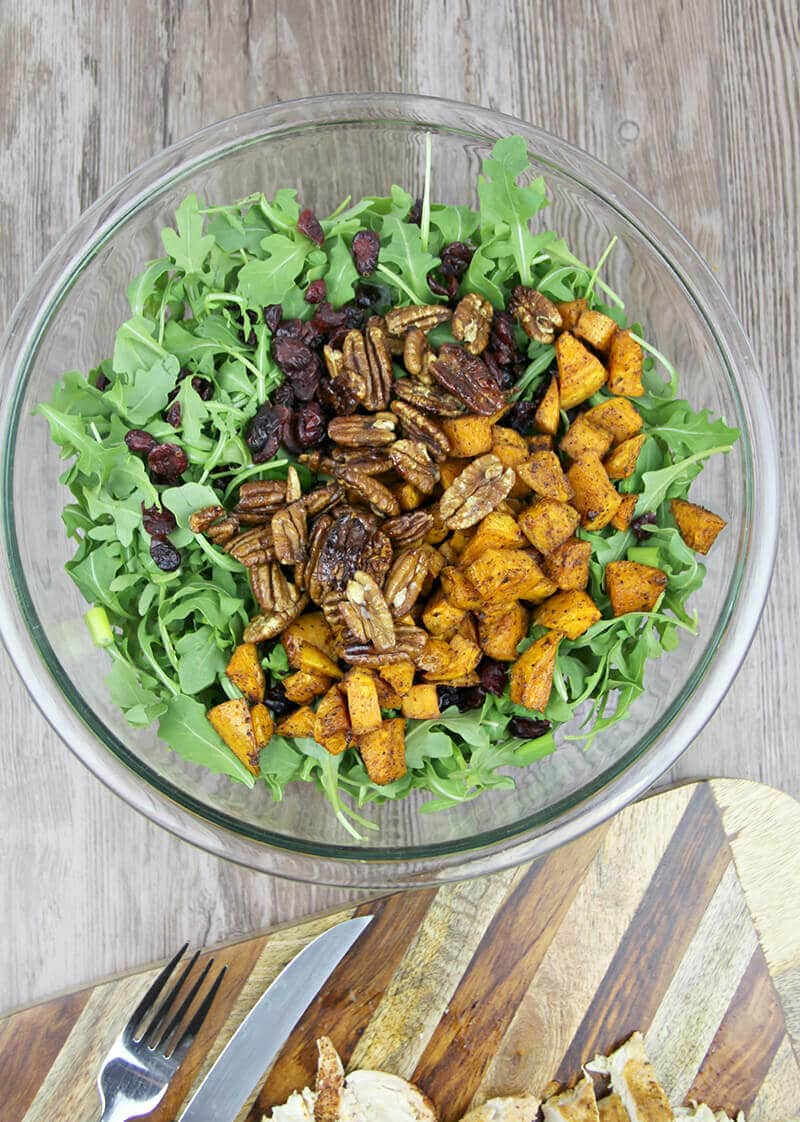 Arugula Salad in bowl with sweet potatoes and pecans.
