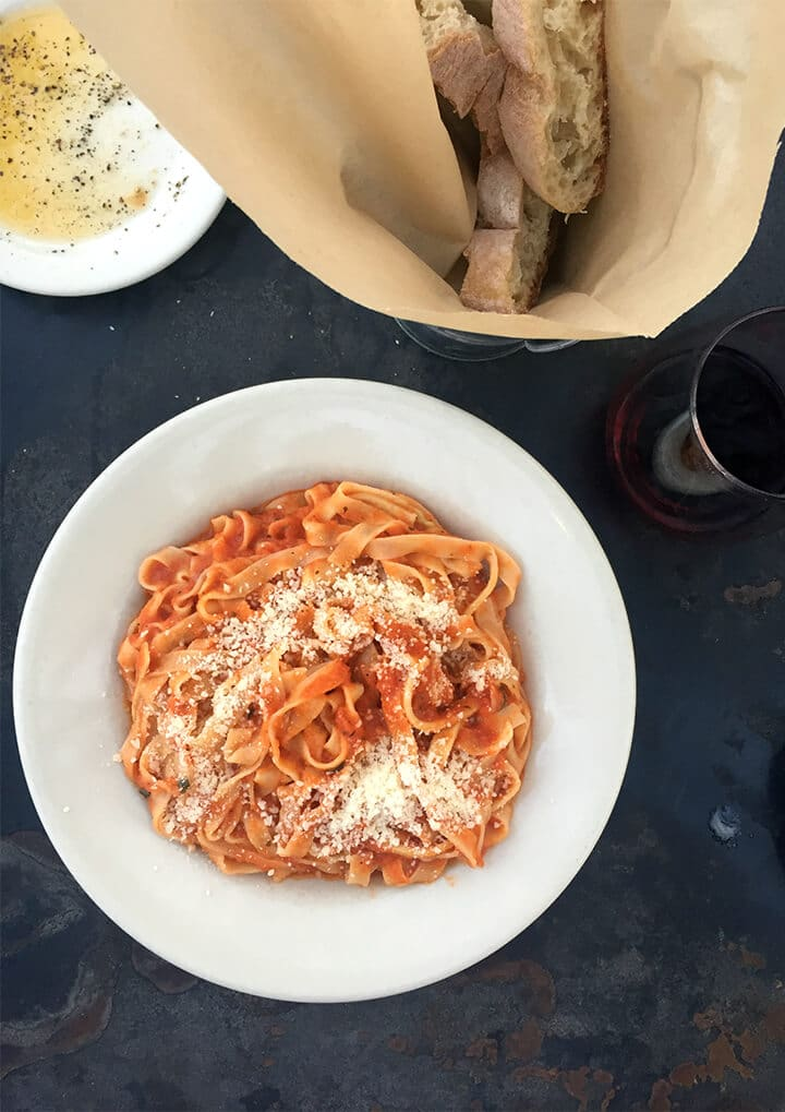 A bowl of pasta next to bread and olive oil from Figo's Pasta in Best Places to Eat in Atlanta.