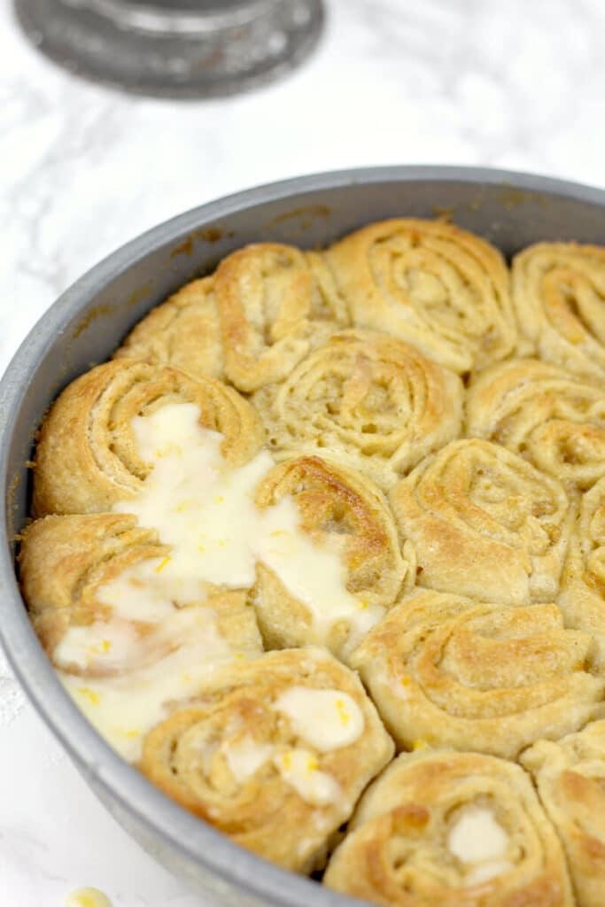 Powdered sugar glaze over orange rolls.