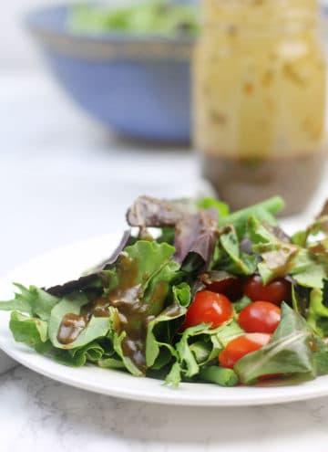 Balsamic Vinaigrette over salad on plate.