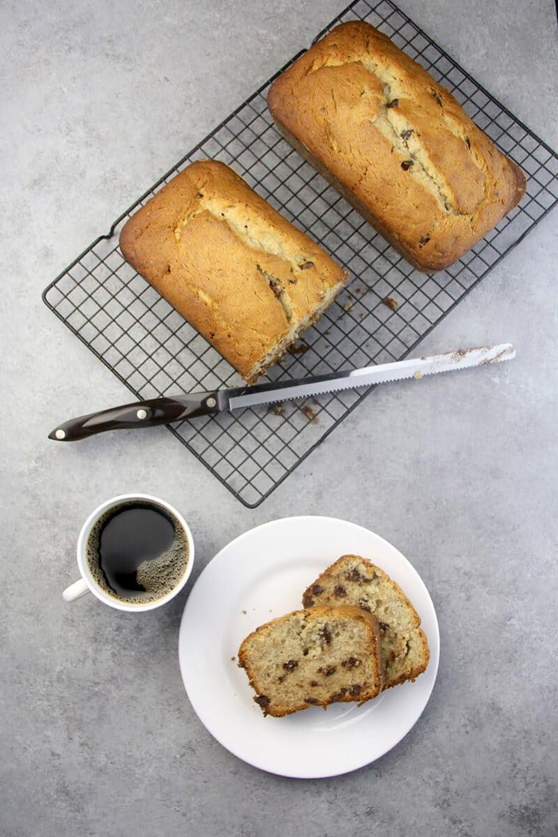Slices of Chocolate Chip Banana Bread and two loaves with a cup of coffee.