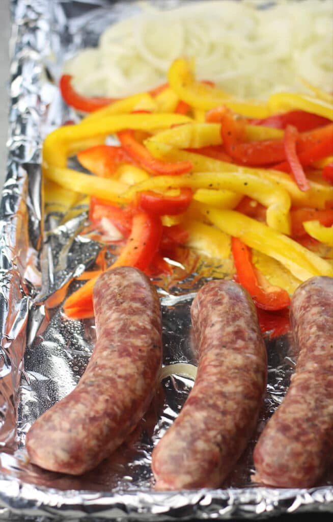 Sausage, Peppers, and Onions on a baking sheet ready to cook.