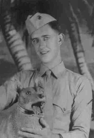Photo of a young service man holding a dog.