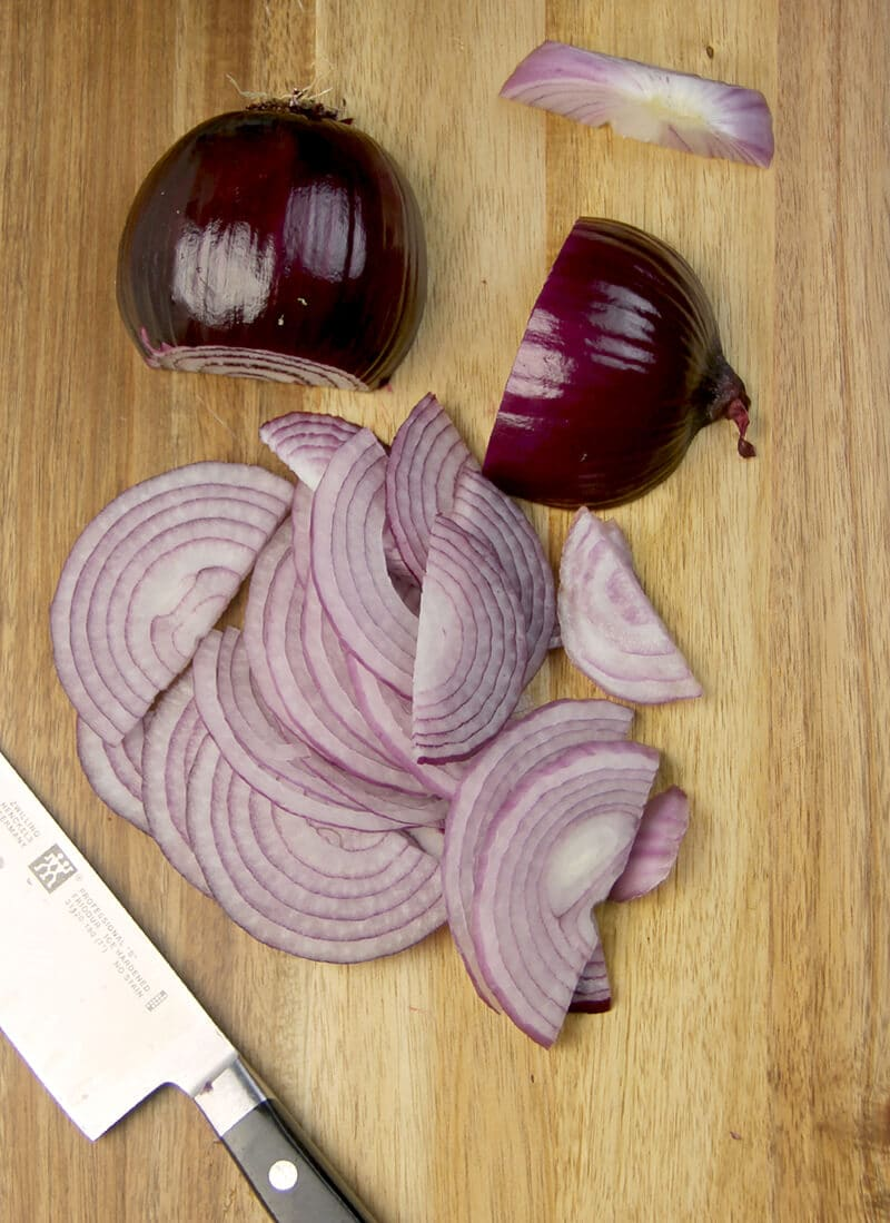 Thinly sliced red onions on a cutting board with a knife.