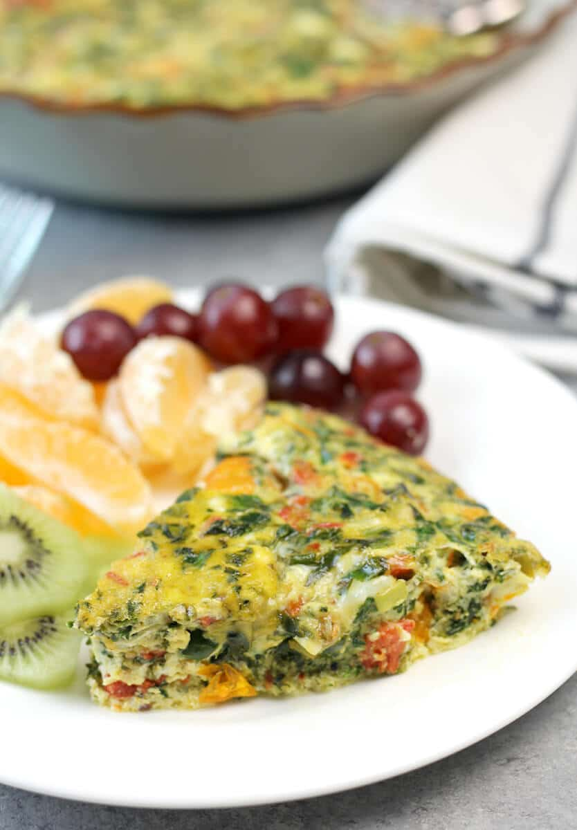 Slice of easy crustless quiche on a plate with grapes and tangerines.