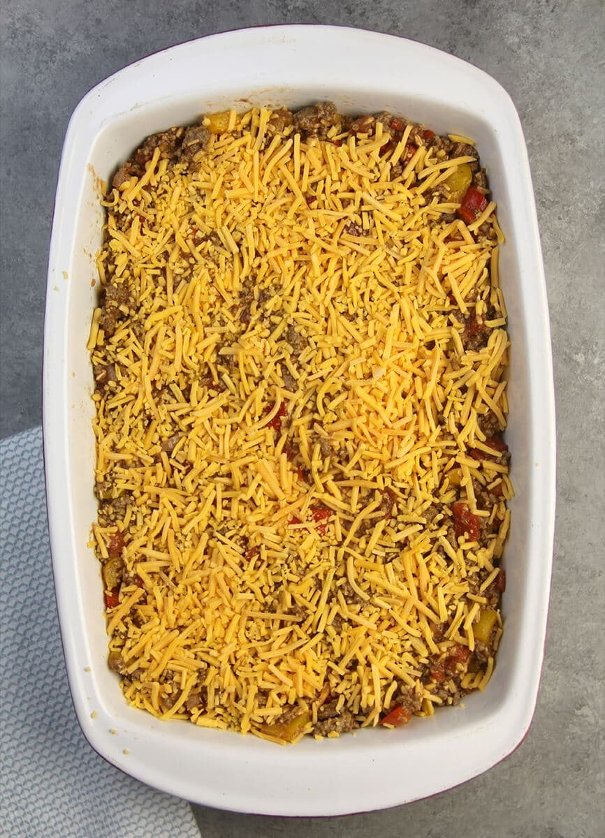 The mixture of meat, farro, and peppers topped with cheese in a baking dish for unstuffed pepper casserole.