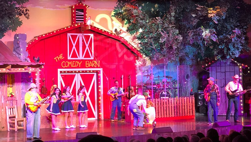 Performers in front of the red barn on the stage at the Comedy Barn in Pigeon Forge.