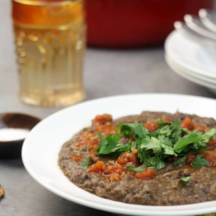 Easy Black Bean Soup in a white bowl garnished with cilantro and salsa.