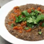 a bowl of black bean soup garnished with parsley