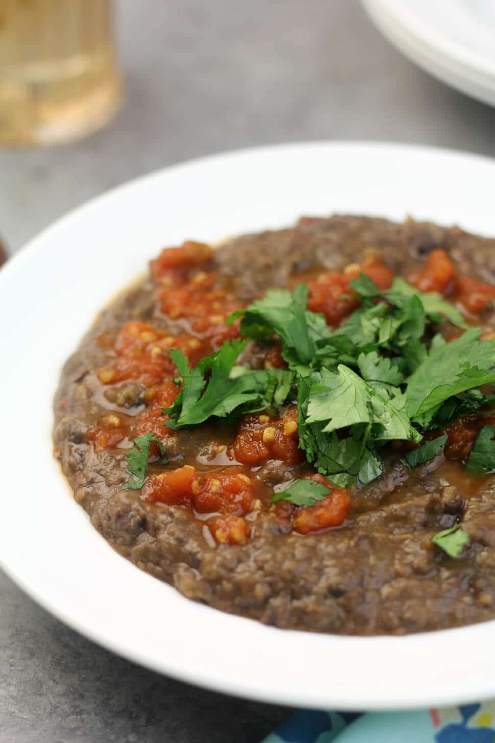 Close up photo of a white bowl filled with easy black bean soup garnished with cilantro and salsa.