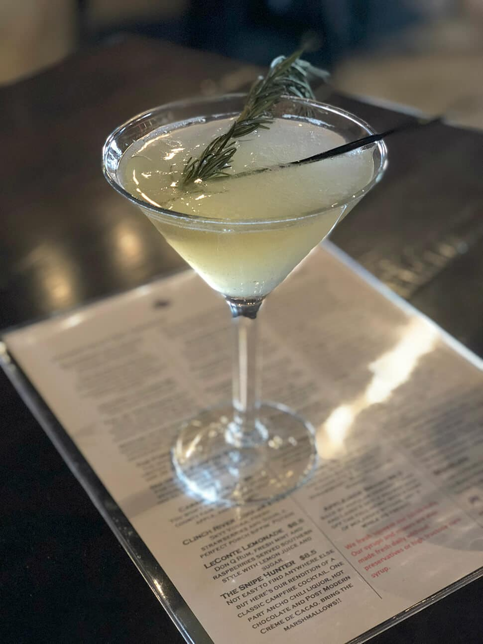 A gin-based cocktail in a coupe glass with a sprig of rosemary at the Local Goat, a favorite of Pigeon Forge restaurants.