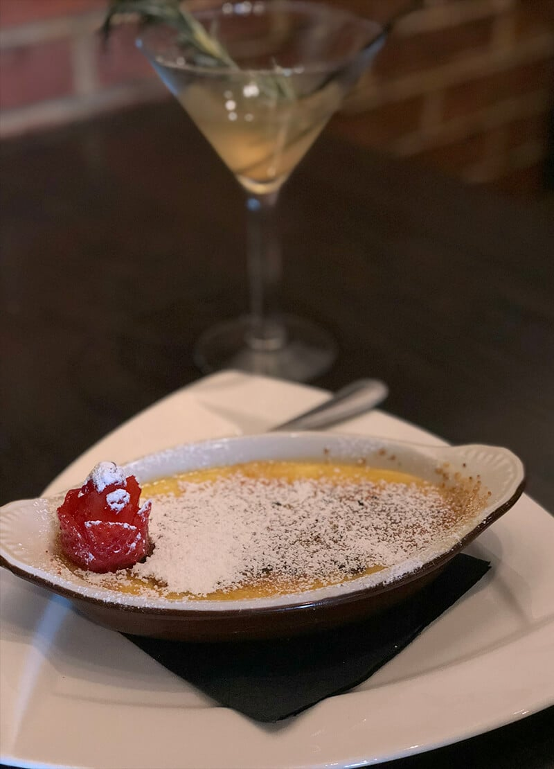 A dish of creme brulee from the Local Goat with a cocktail glass in the background.