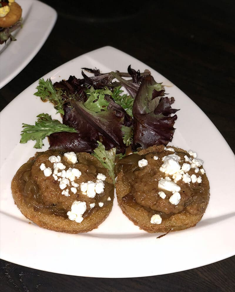 Pigeon Forge restaurants include Local Goat where they offer this plate of fried green tomatoes with bacon jam and goat cheese on top.