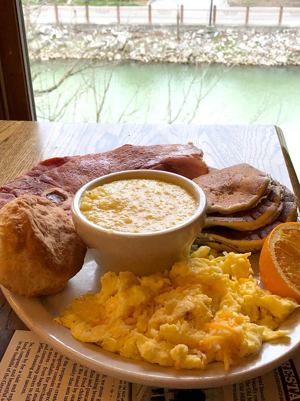 A plate of eggs, grits, and ham on a table that looks out to the river in Pigeon Forge at the Old Mill Restaurant.