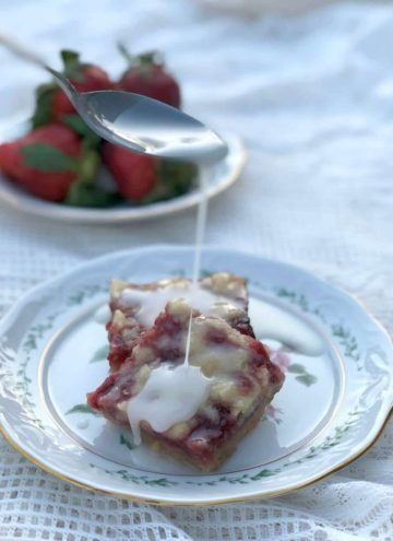 Strawberry Bars on a plate with a spoon drizzling lemon glaze.