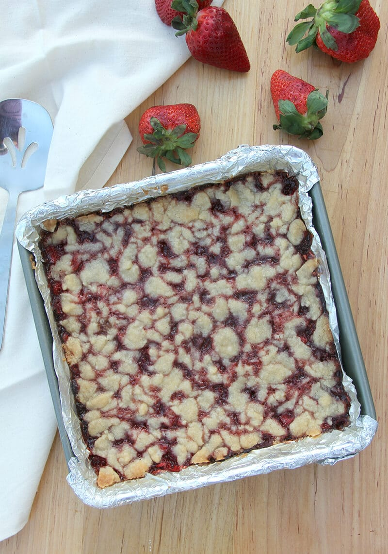 Baked strawberry bars in a baking pan with strawberries on the side.