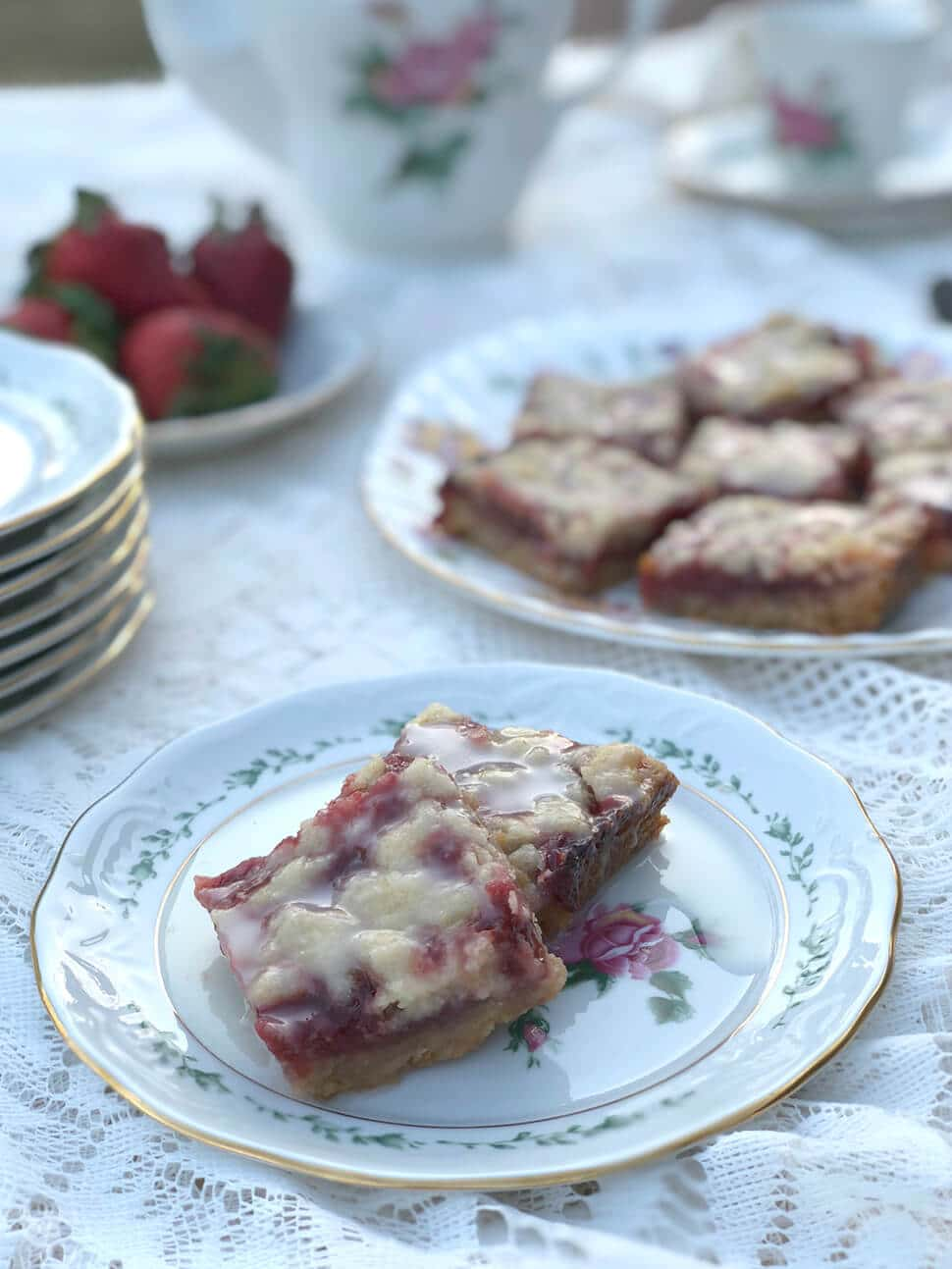Two strawberry bars on a plate for serving with a platter in the background.