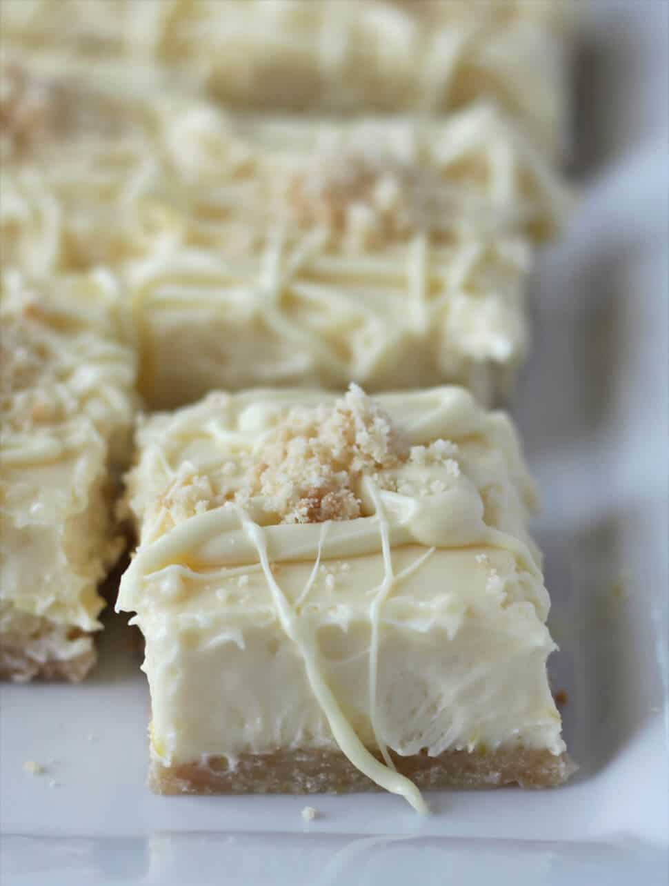 Side view of white chocolate cheesecake bars on a serving platter.