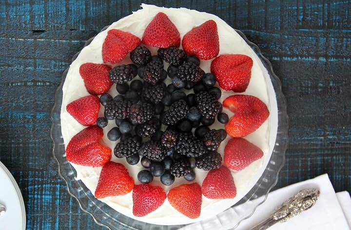 Overhead photo of patriotic cake with strawberries and blueberries.