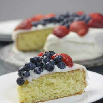 A slice of red white blue cake on a plate with berries.