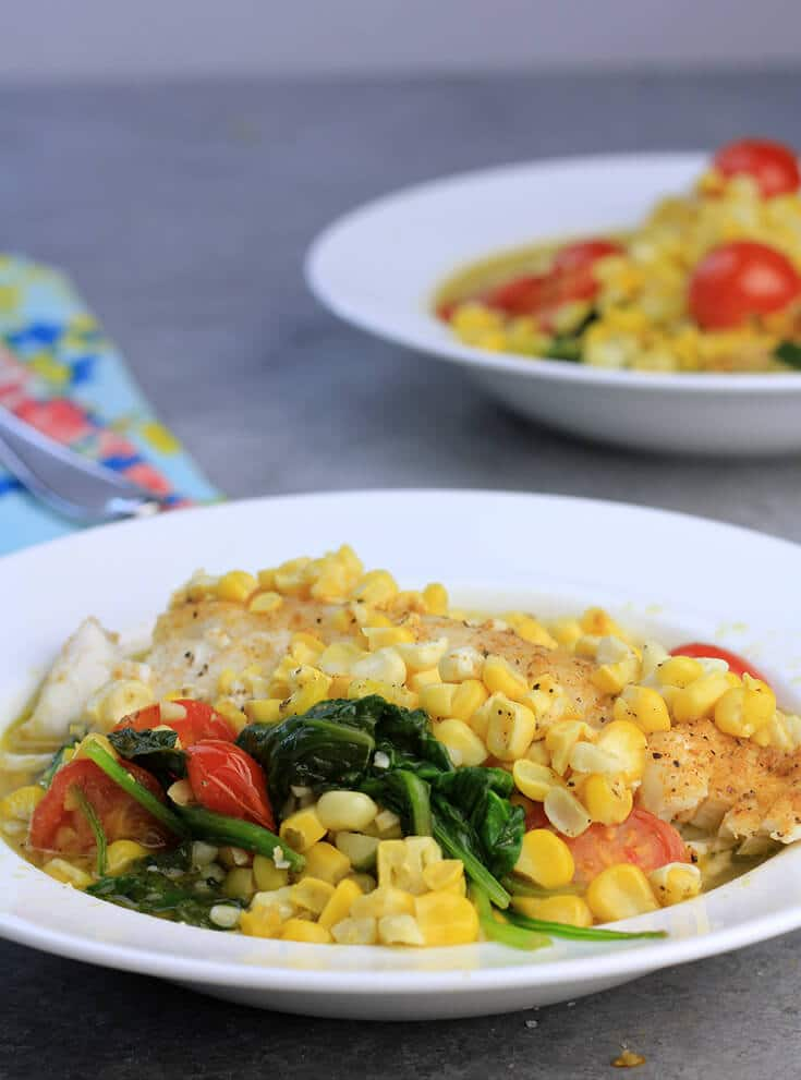 Oven baked fish with corn and tomatoes in a bowl.