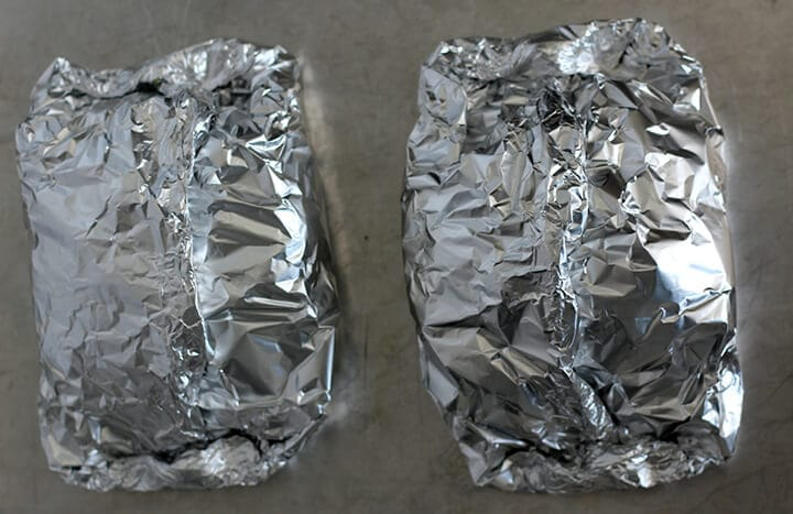 Sealed foil packets on baking sheet with oven baked fish.