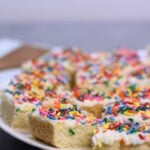 Sugar Cookie Bars with sprinkles and frosting on a plate.