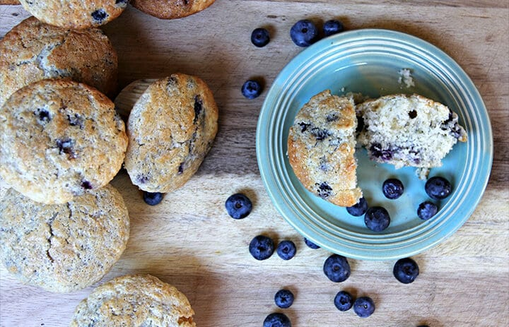Overhead photo of blueberry muffins with a muffin on a plate.