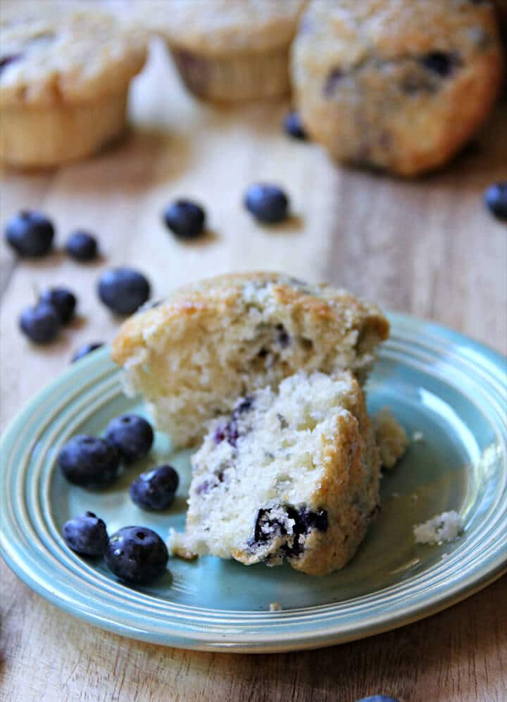 Blueberry muffins on a plate with blueberries and muffins in the background.