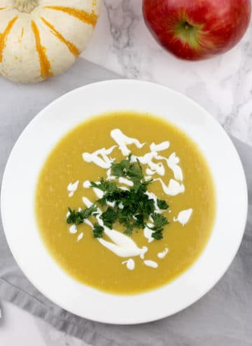 A bowl of butternut squash soup drizzled with sour cream and parsley.