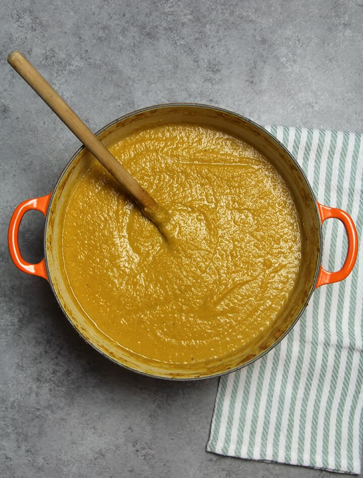 A finished pot of butternut squash soup with a wooden spoon in it.
