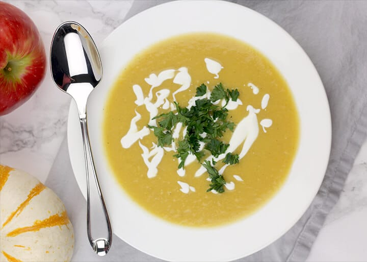 Butternut squash soup in a bowl with a spoon on the side.
