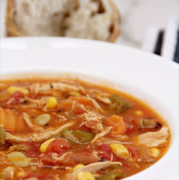 A bowl of chicken vegetable soup with bread in the background.