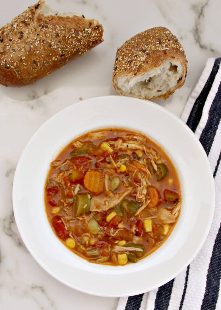 Chicken and vegetable soup in a bowl with bread beside it.