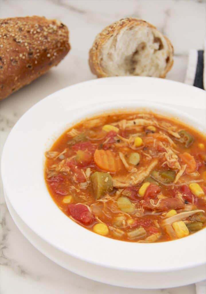 Chicken vegetable soup in a bowl with bread.