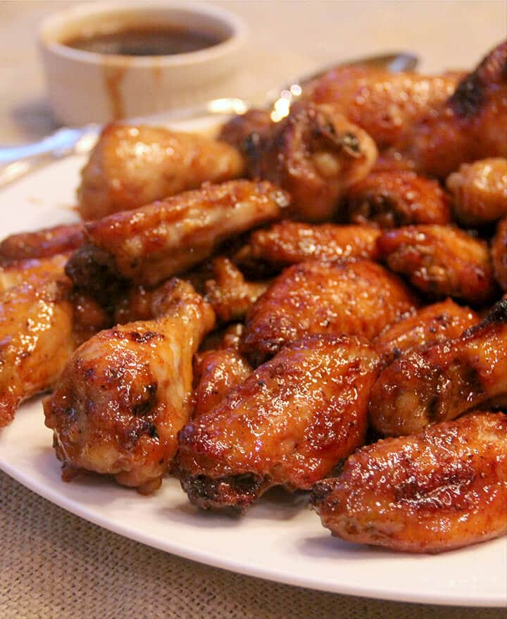 A plate of baked chicken wings with honey sriracha sauce.