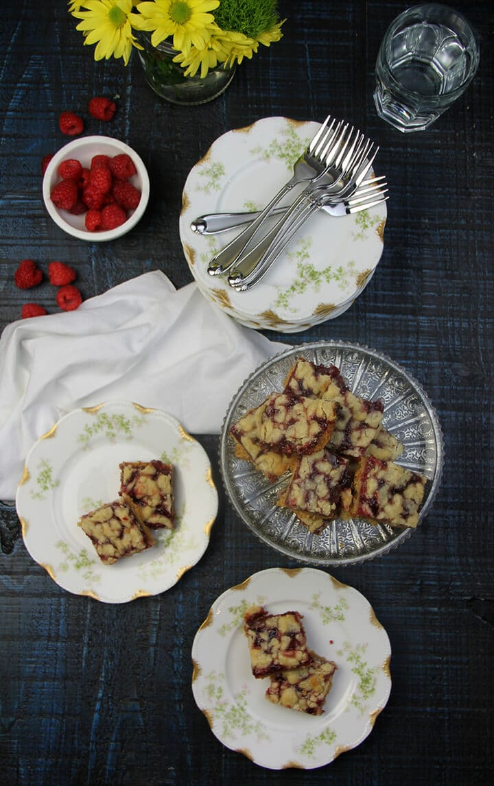 A platter of raspberry bars with more bars on plates next to it.