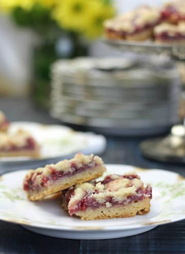 Raspberry bars on a plate with the platter in the background.