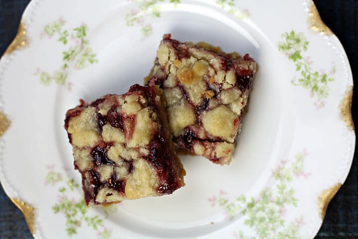 Two raspberry bars on a plate.