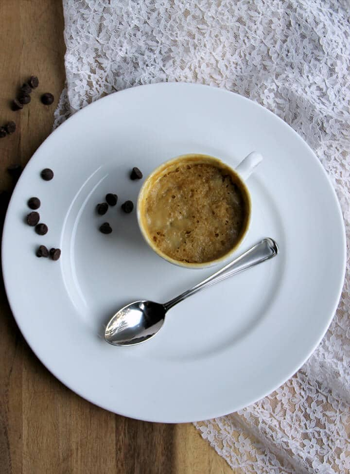 Overhead photo of a full cookie in a mug with a spoon on a white plate.