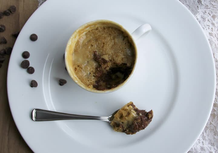 Spoonful of cookie in a mug on a plate with the mug.