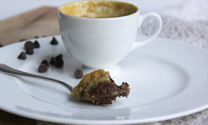 A spoonful of chocolate chip cookie in a mug on a plate next to the cup.