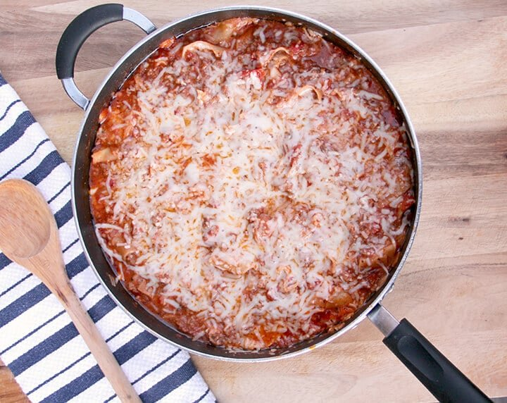A skillet with cheesy lasagna with a wooden spoon next to it for a romantic dinner at home.