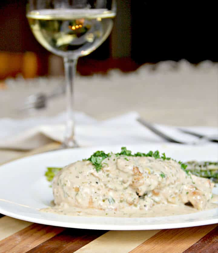 Chicken with mustard sauce on a white plate with a glass of wine in the background for a perfect romantic dinner at home.