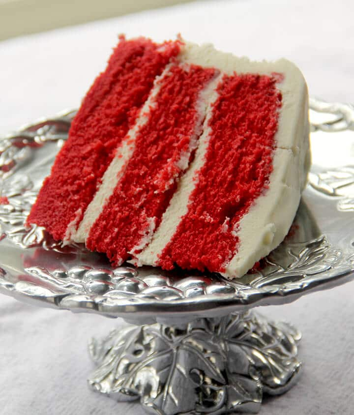 Slice of red velvet cake on a silver platter for dessert for a romantic dinner at home.