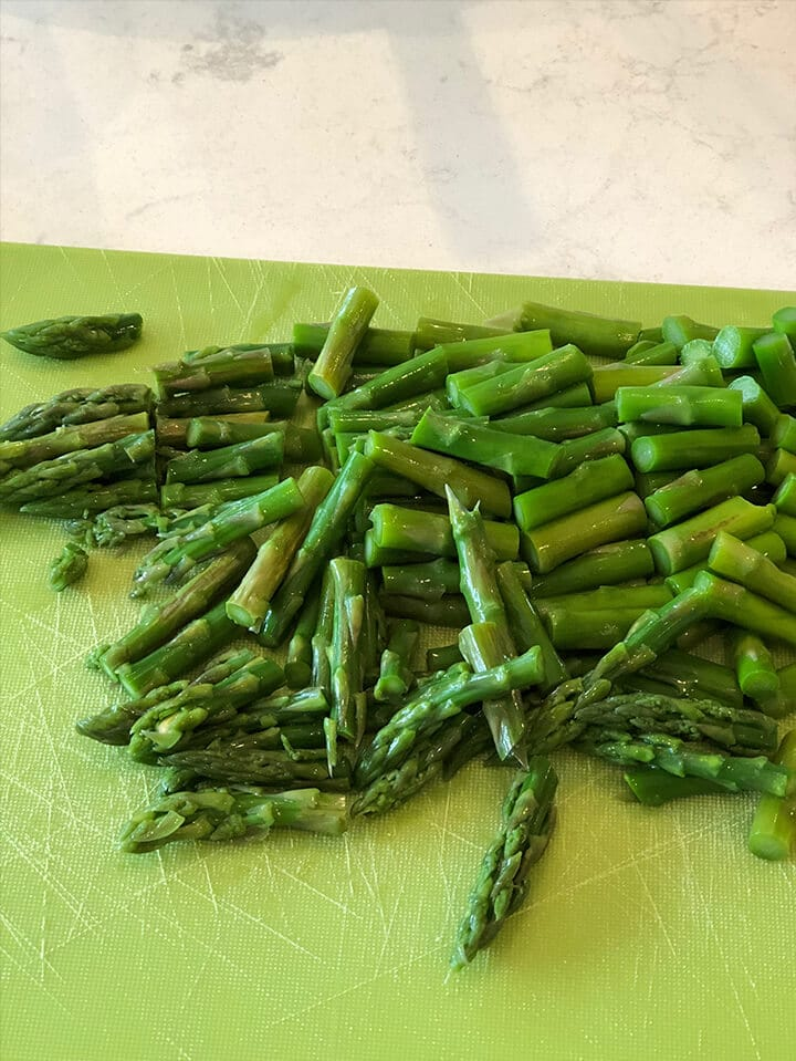 Chopped asparagus on a cutting board for pasta salad.