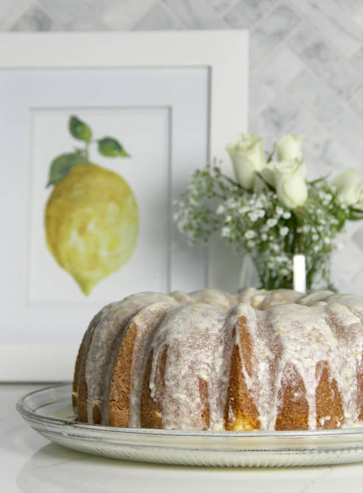 A pound cake drizzled with lemon glaze icing with a vase of flowers in the background.