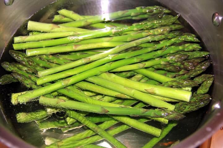 Asparagus in a bowl of ice water to stop the cooking.